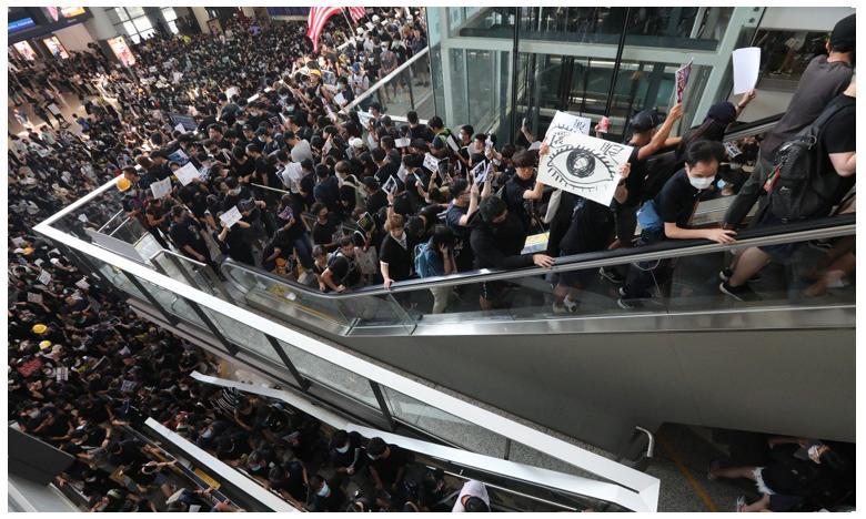 Hong Kong grounds all flights as protest paralyzes airport, ఎయిర్పోర్టులోకి దూసుకొచ్చిన నిరసనకారులు.. విమాన రాకపోకలు రద్దు