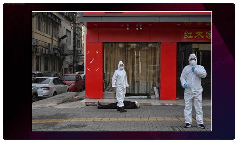 A grey-haired man wearing a face mask lies dead on the pavement at ground zero, కరోనా..వూహాన్ రోడ్డు ఫుట్పాత్పై డెడ్బాడీ.. నిర్మానుష్యమైన నగరం